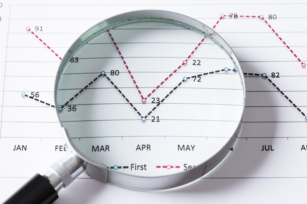 Magnifing glass and documents with analytics data lying on table .jpeg