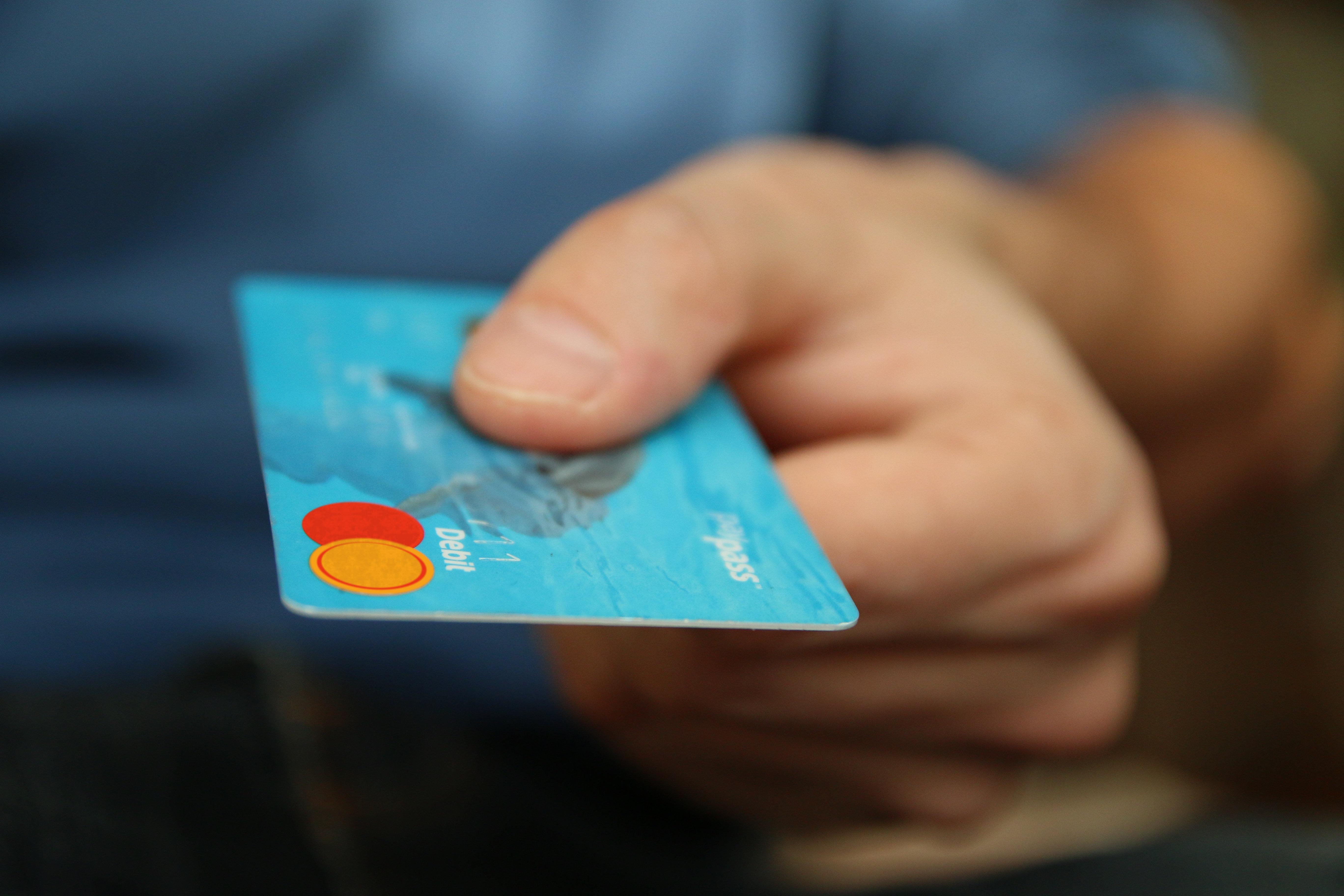 A hand holding a debit card.